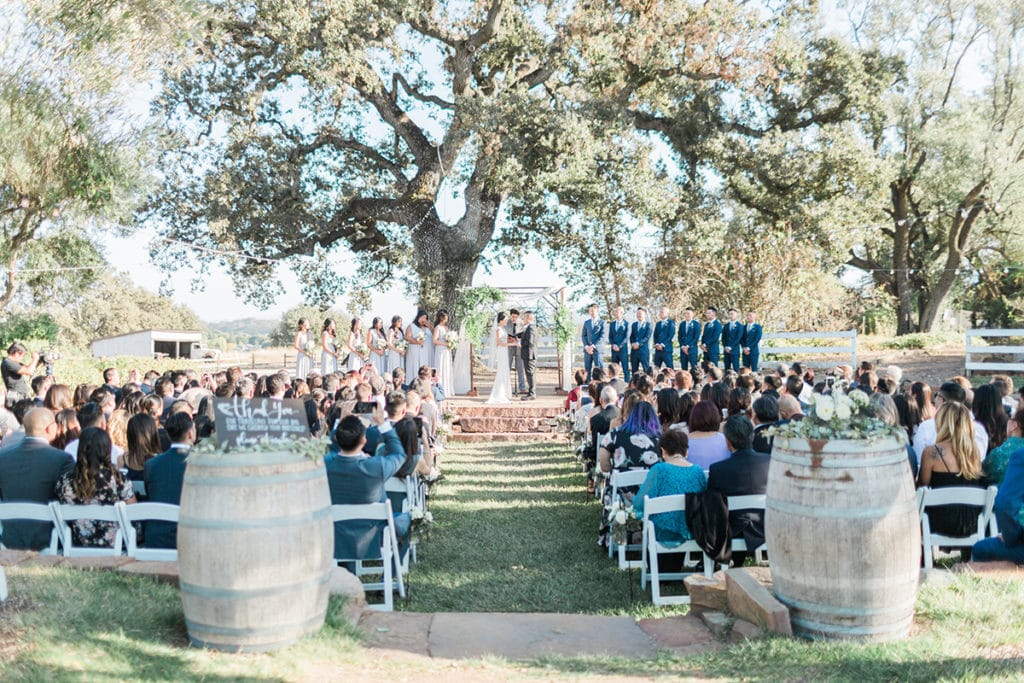 Ceremony under a large oak tree with wooden chuppah decorated with white fabric and green garland