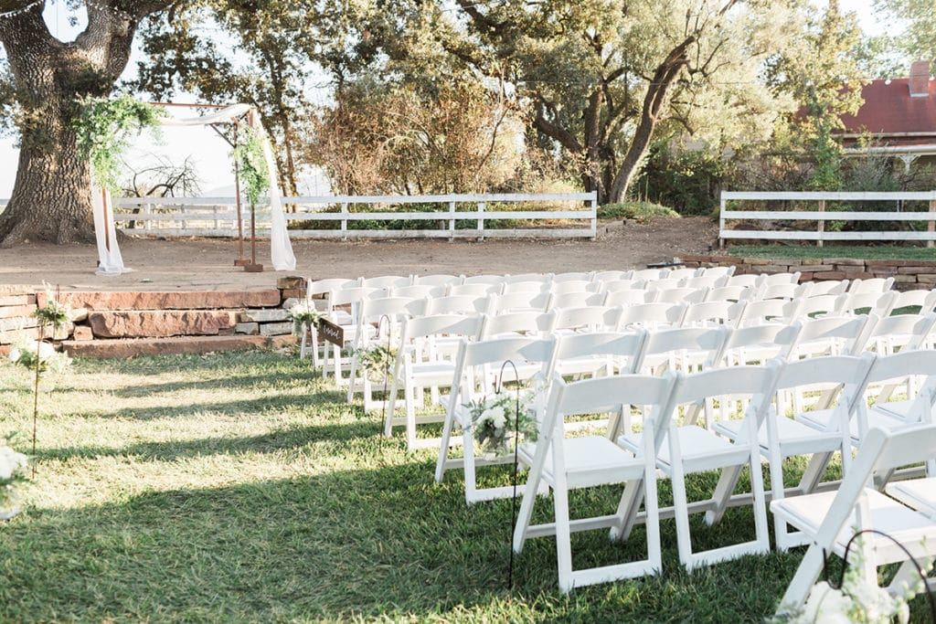 Ceremony set up outside rustic Barn in California. Wooden chuppah with white flowy fabric and greenery