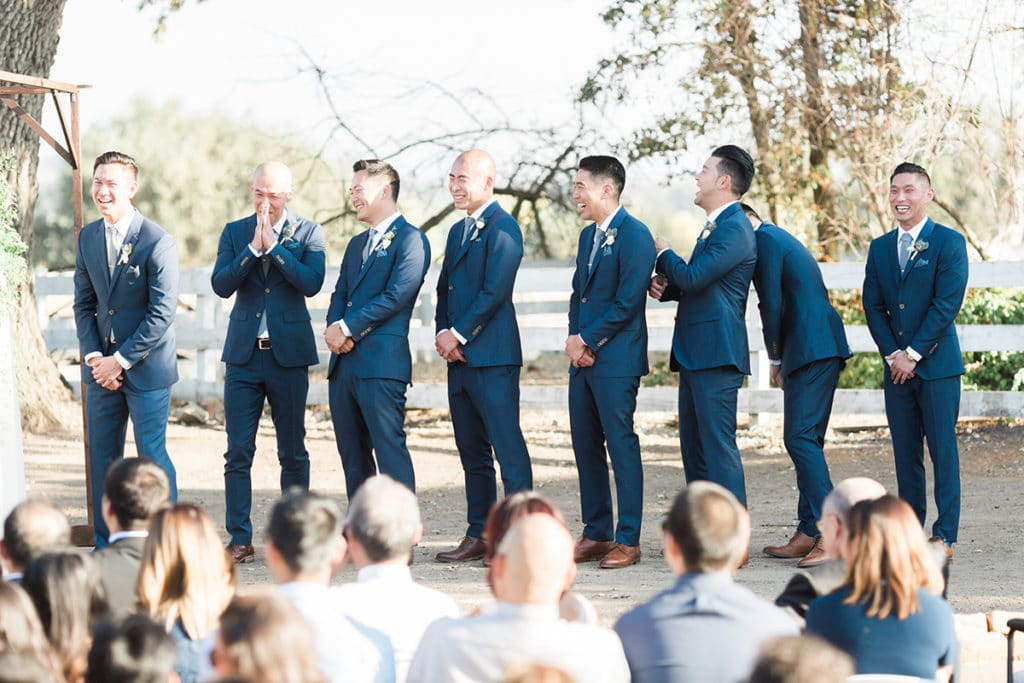 groomsmen laughing when groom reads his funny vows to his bride