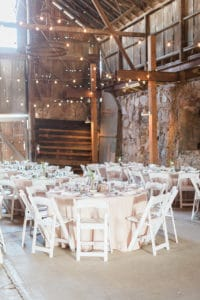 Barn wedding with bistro lights and stone walls