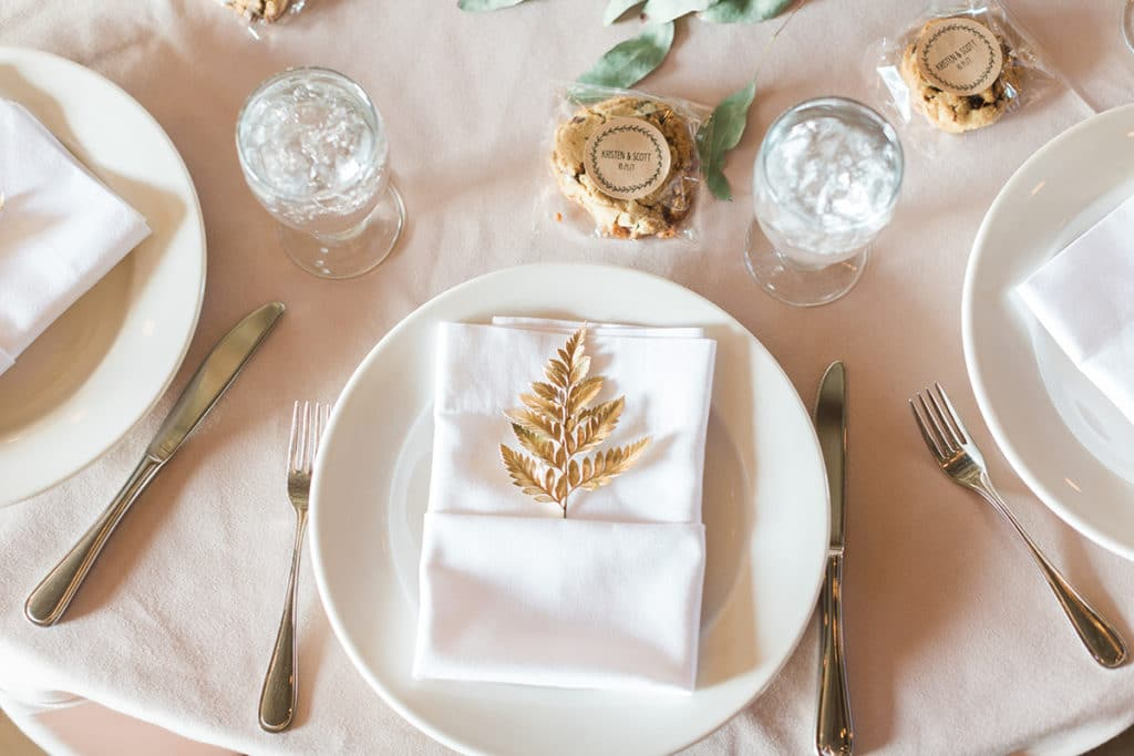 White plates with gold fern on white napkin and cookies as wedding favors