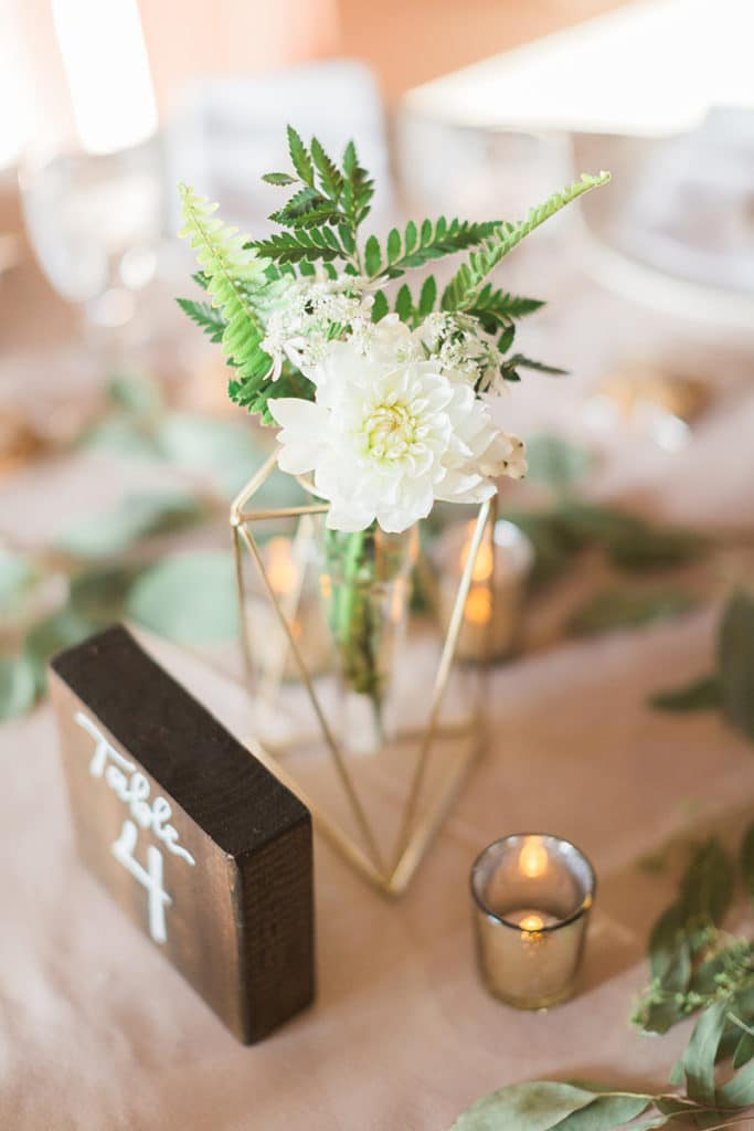 White flowers with greenery inside modern gold geometric vase