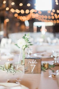 Wooden table numbers with white and green florals