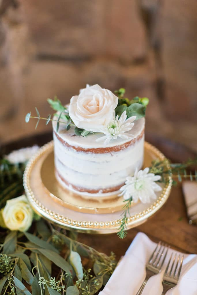 Single tier Naked Cake with white flowers and greenery on wooden wine barrel