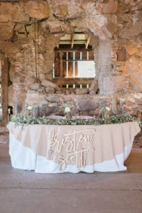 Sweetheart table inside old barn with green garland and wooden laser cutouts of bride and groom names