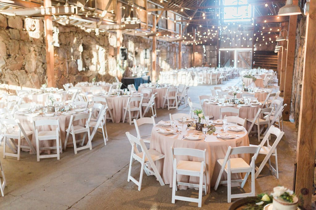 Round tables and cream linens with white and green flowers set up inside old historic barn for wedding reception