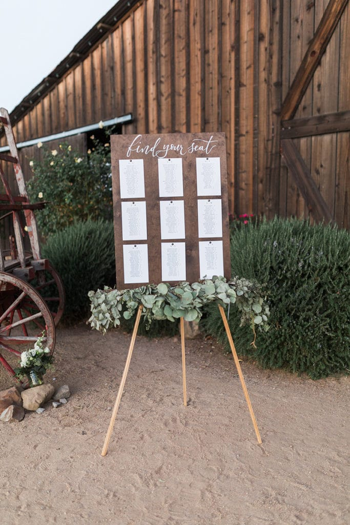 Wooden seating chart with green garland for rustic barn wedding