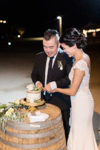 Bride and groom cut a simple naked cake on wine barrel