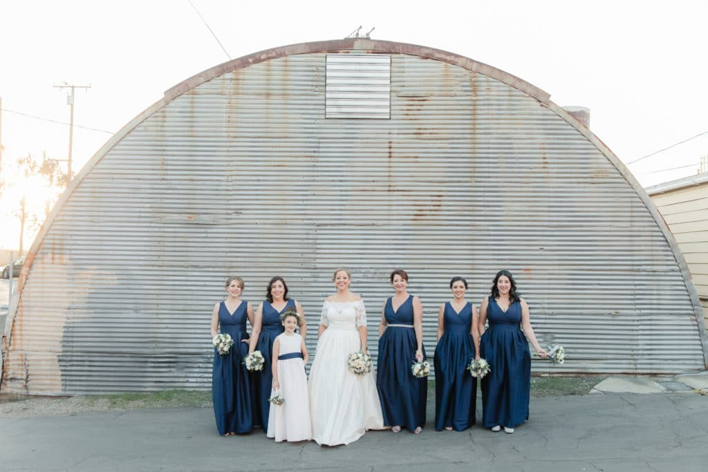 Bride and bridesmaids in navy with white bouquets in front of Smoky Hollow Studios