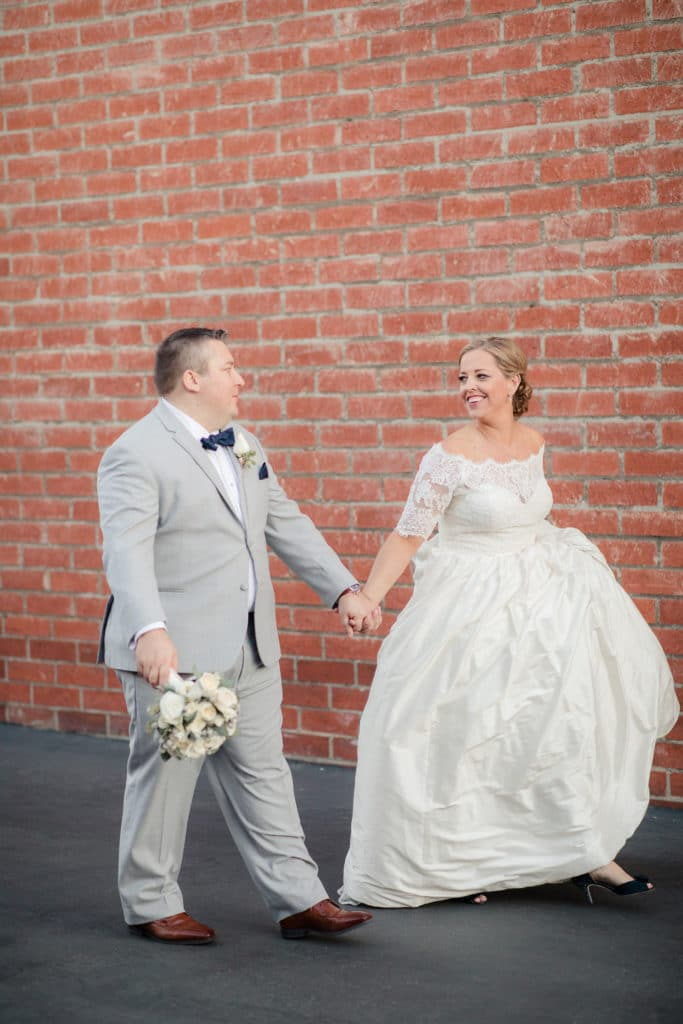 Bride and groom in navy and light grey in front of brick wall at Smoky Hollow Studios