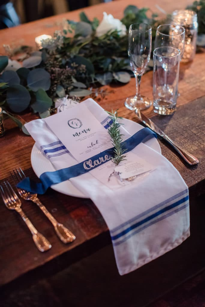 Navy and white details on wooden farm table for wedding reception with rosemary spring and glitter names on navy ribbon