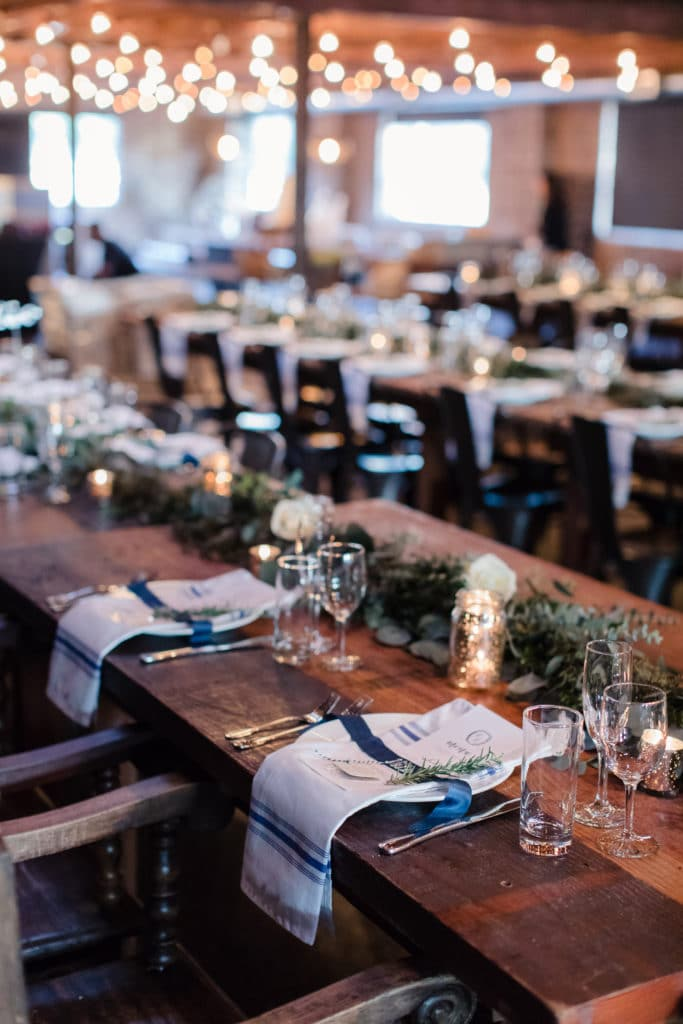 Navy and white wedding decor on long wooden tables at Smoky Hollow Studios