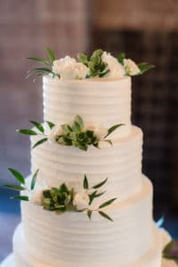 4 tiered white wedding cake with white flowers and greenery