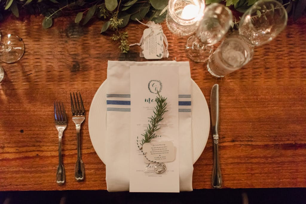 Rustic wedding place setting with white plate, navy and white farm napkin and sprig of rosemary