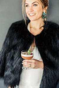 bride with black faux fur coat and delicious cocktail in hand