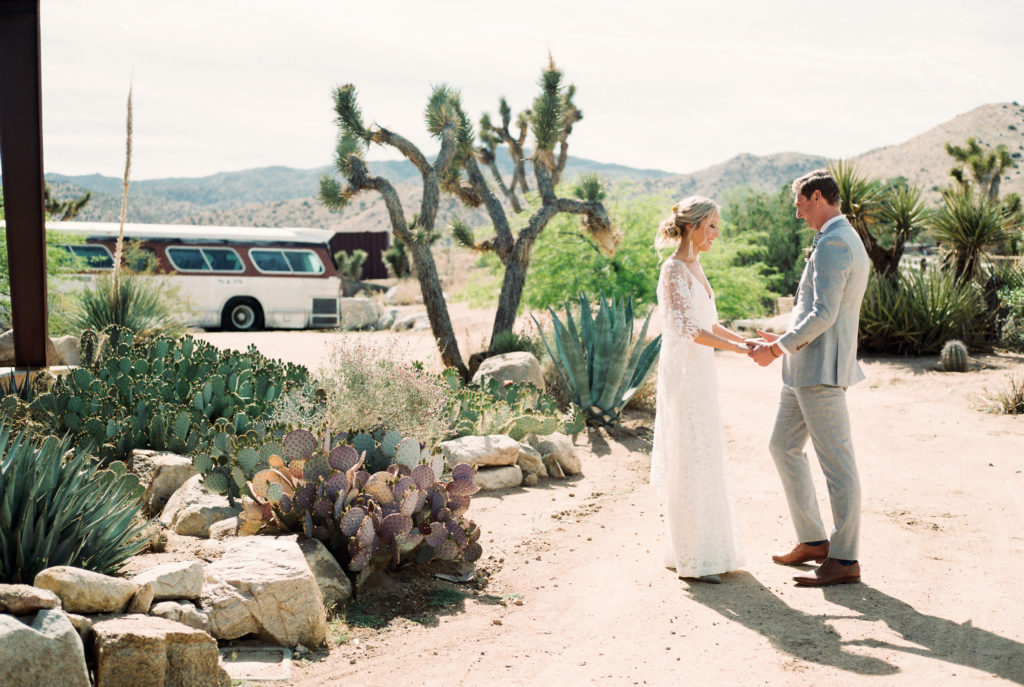 Boho bride and groom at Rimrock Ranch in Joshua Tree with vintage bus and joshua trees