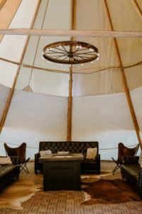Under Canvas Moab reception tent with leather couches, chandeliers and a propane fire pit