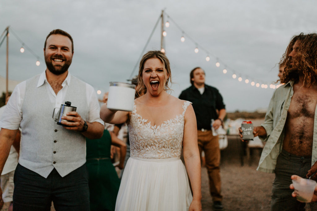 Bride and groom laughing and cheers with bistro lights behind them in the desert