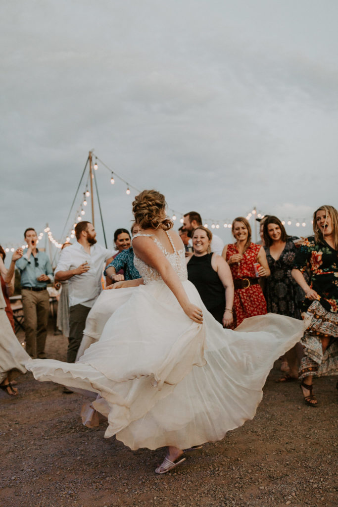 Bride dancing in the desert with bistro lights
