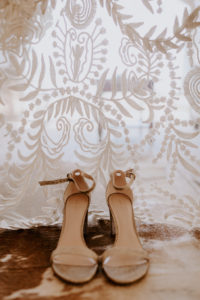 Nude wedding sandals in front of lace Rue de Seine gown