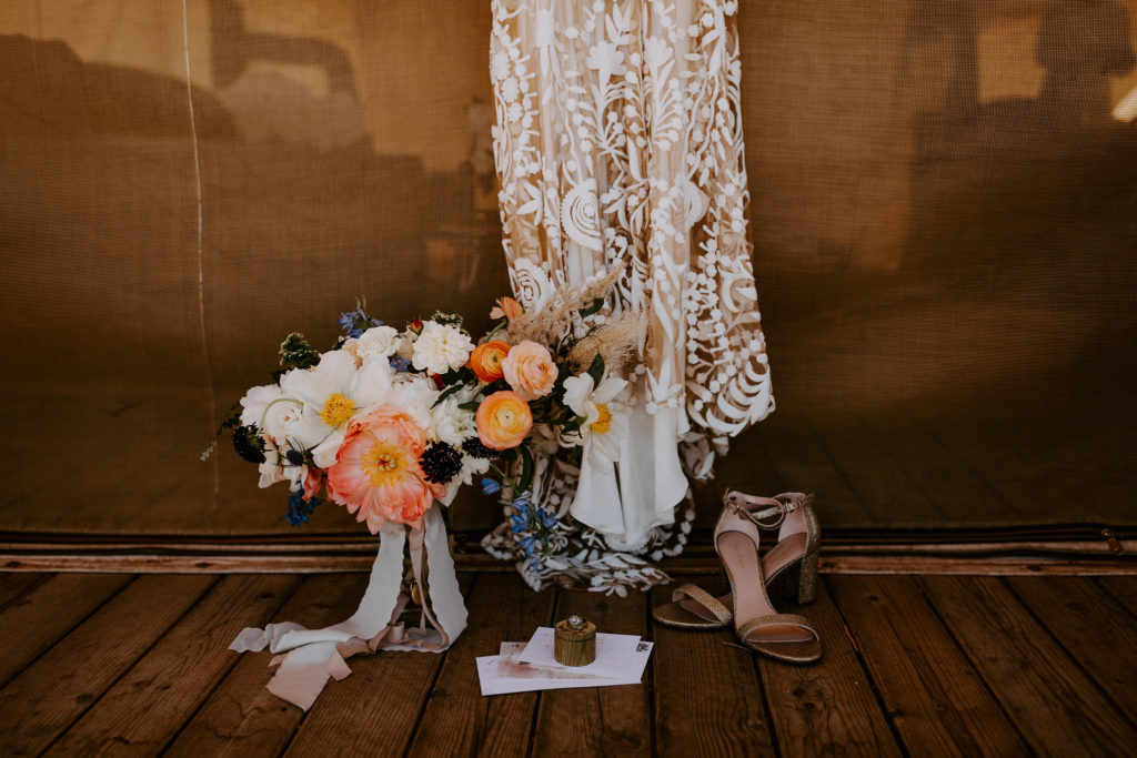 Wild boho bouquet and Rue de Seine gown in front of teepee