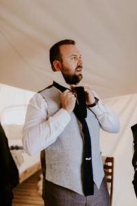 Groom putting his tie on inside under Canvas moab tent