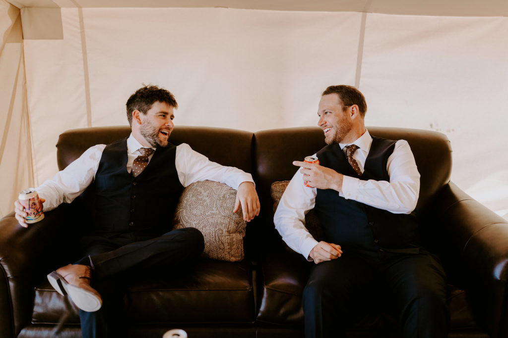 Groomsmen laughing at Under canvas moab wedding