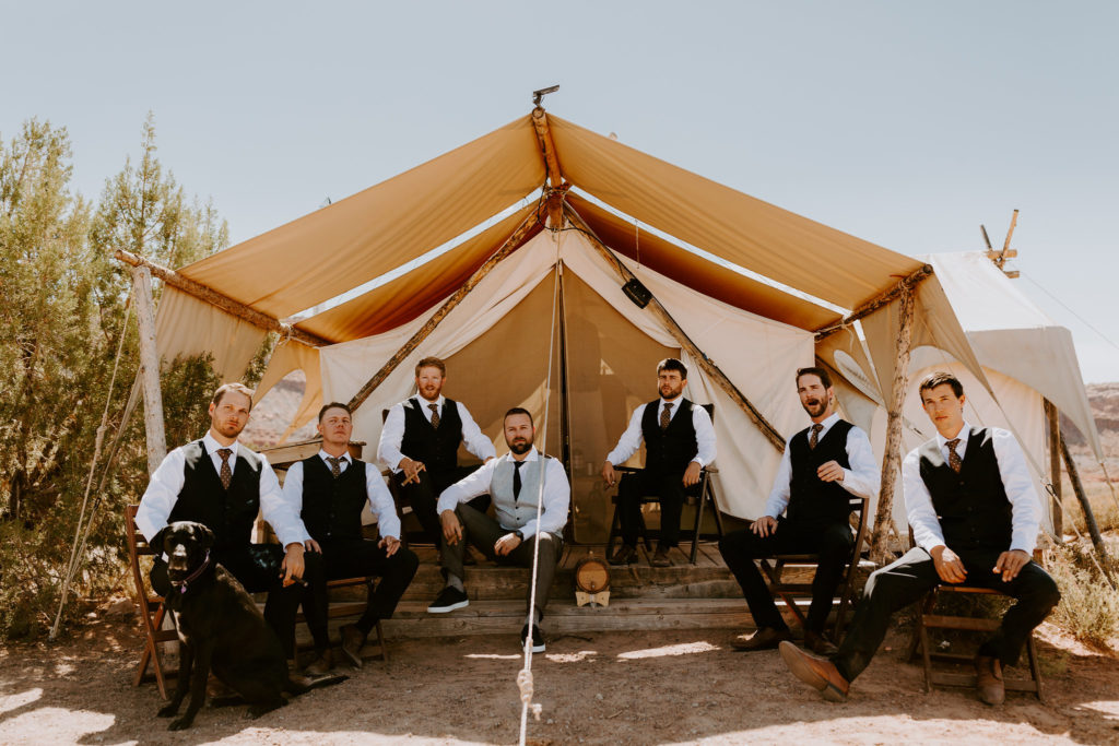 Groom and groomsmen in front of tent at Under Canvas Moab. Desert wedding