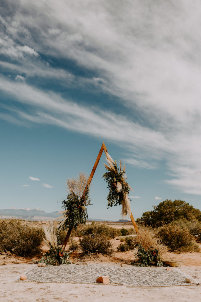 Triangle arch with florals in the desert. Wedding at Moab Under Canvas