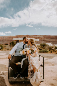 Newlyweds ride away after ceremony in golf cart at Under Canvas Moab