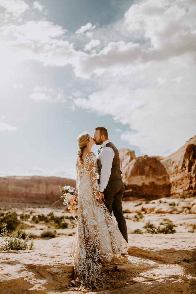 Bride and groom kiss surrounded by red rocks at Under Canvas Moab