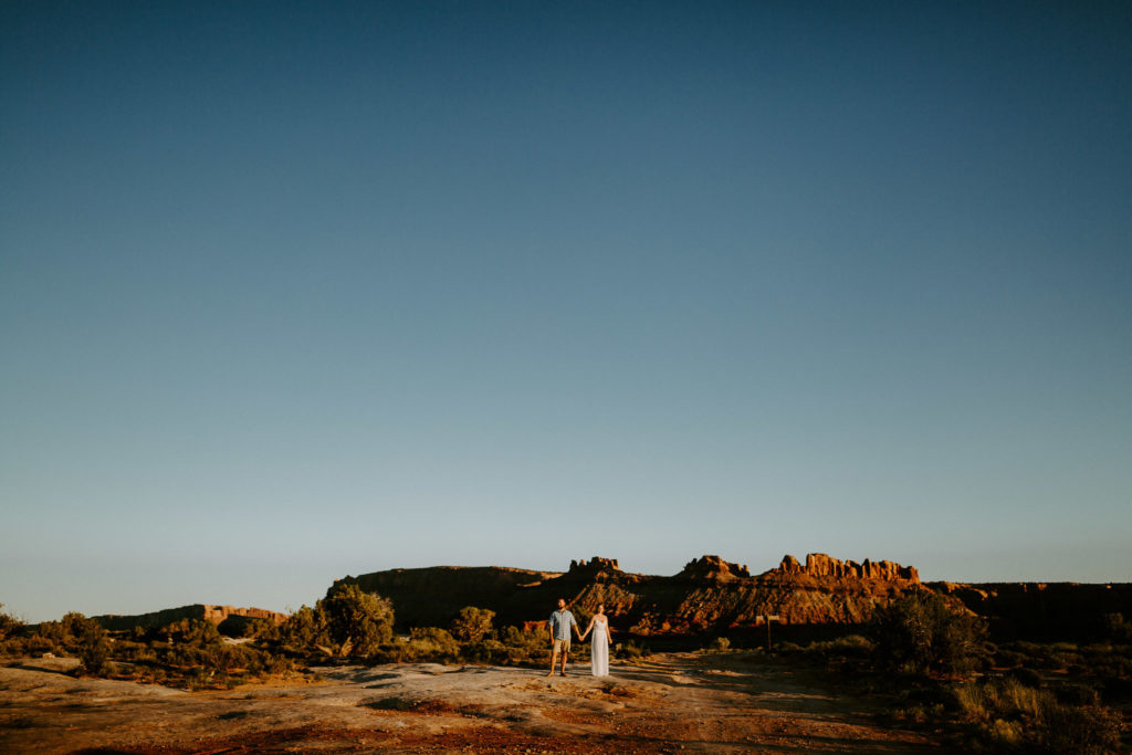 Bride and groom holding hands in the middle of the desert