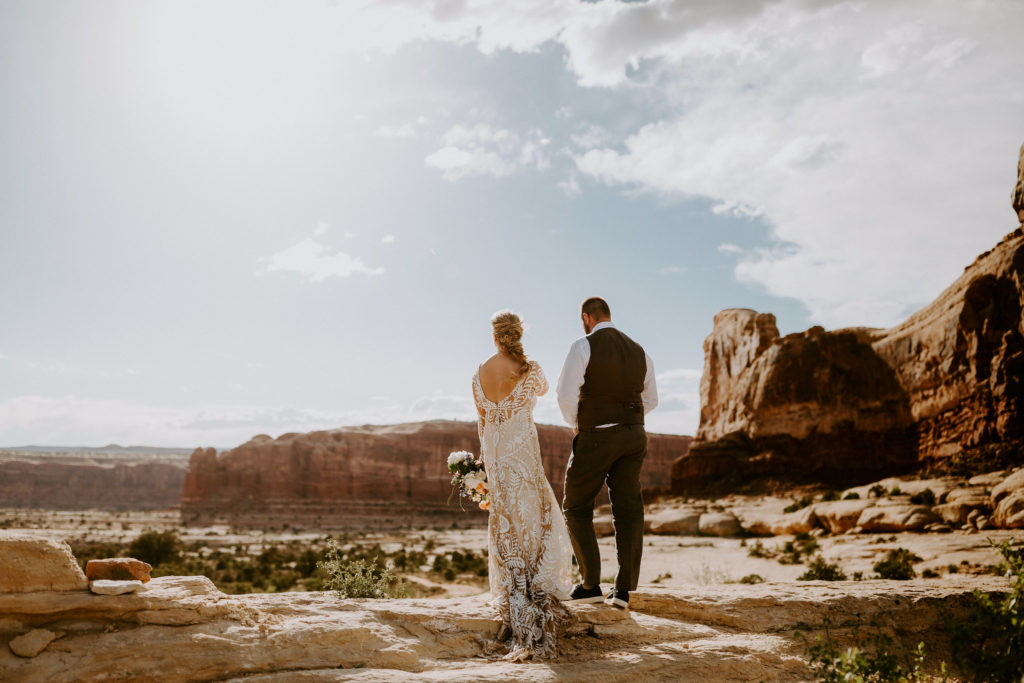 Bride and groom walk into the sunset after wedding at Under Canvas Moab