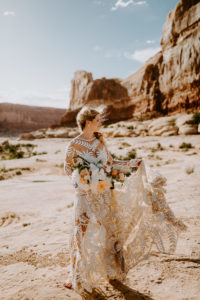 Bride in Rue de Seine gown with lace and moody wild bouquet. Wedding in the desert at Under Canvas Moab