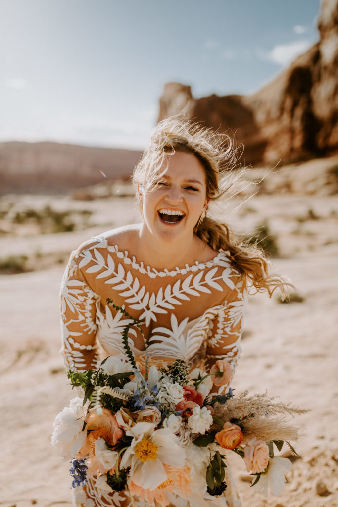 Bride laughing with long messy braid. Desert wedding at Under Canvas Moab