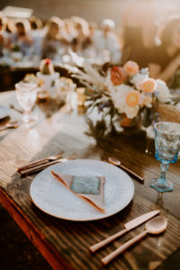 Table setting in Moab desert with gold flatware and colored wine glasses
