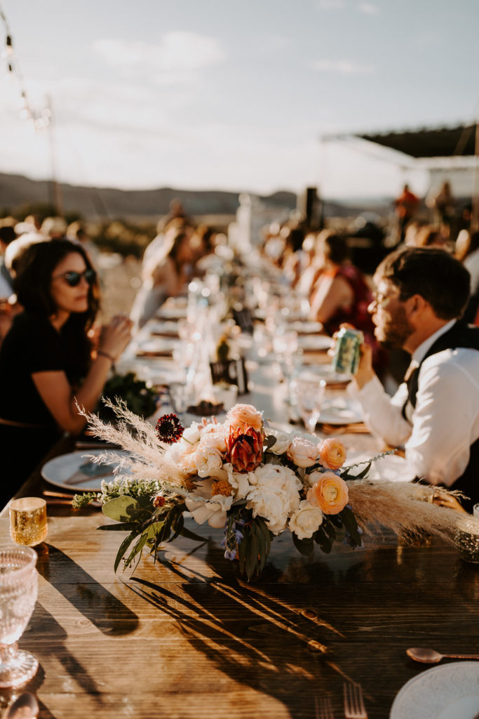 Long family tables in the desert with moody flowers and colored wine glasses. Moab Under Canvas Wedding