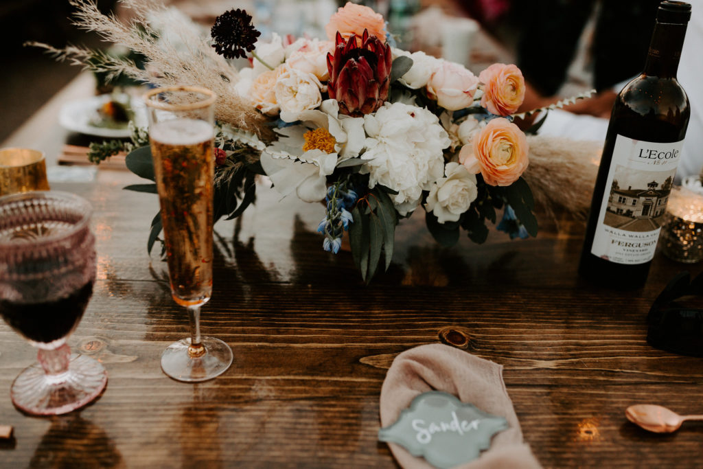 Moody sweetheart table florals on wooden table