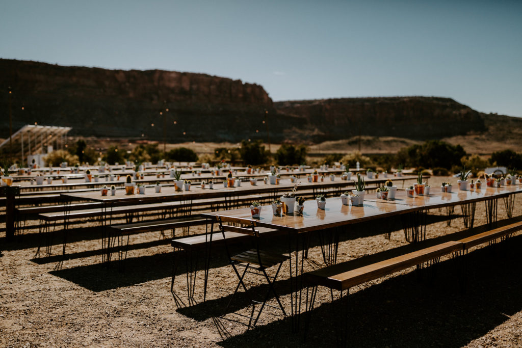 Long wooden tables in the desert for boho wedding at Under Canvas Moab