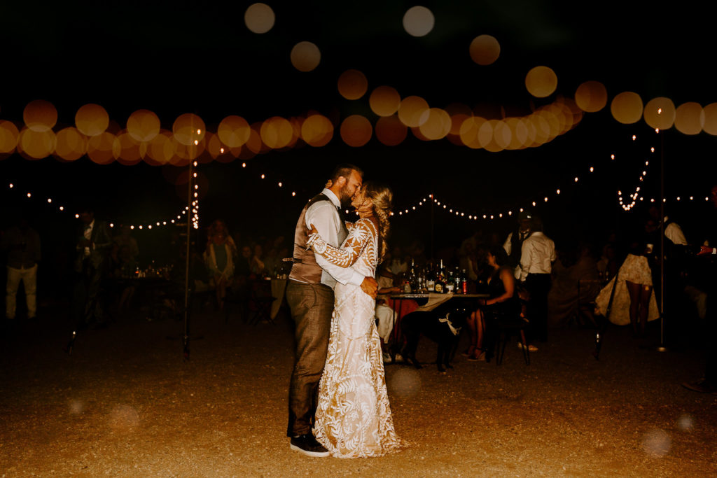 Bride and groom dance under the stars in the desert after weekend wedding at Under Canvas Moab