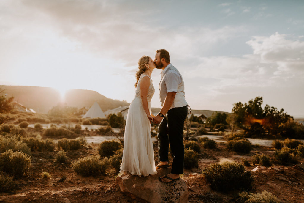bride and groom kiss in the desert at under canvas moab