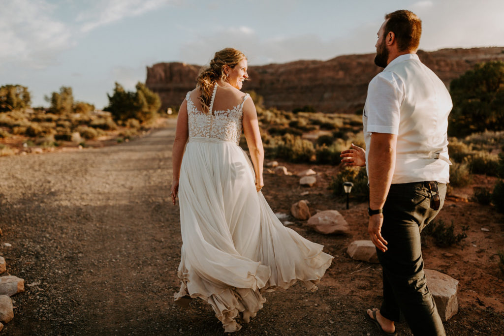 Bride running away and laughing in the desert in Moab