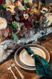 Holiday table decor on wooden table with velvet green napkin. Decorated with a faux fur table runner and burgundy and green florals