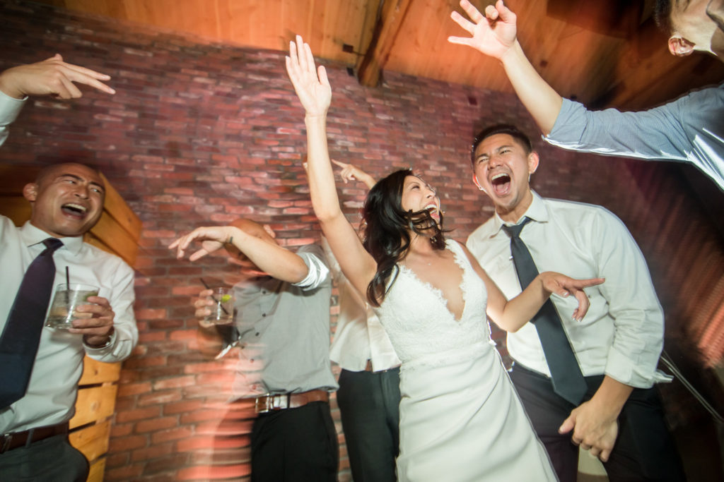 Modern bride and groomsmen celebrating and dancing during reception at The Colony House wedding