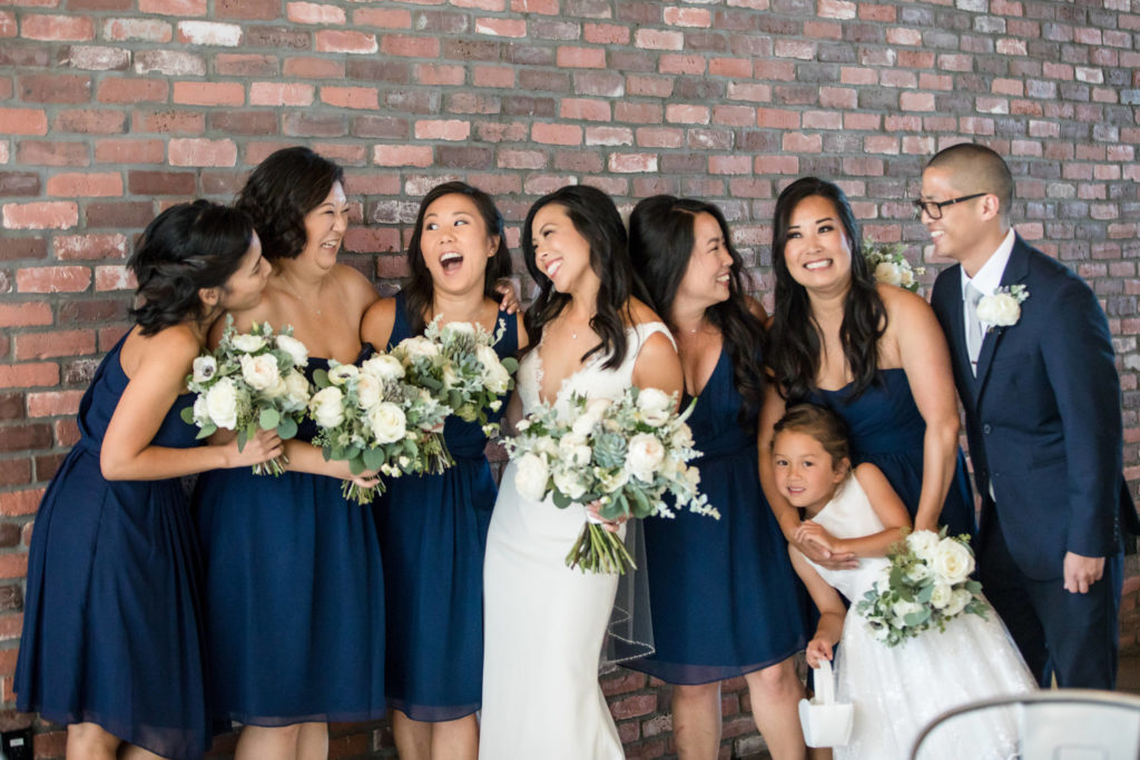 Bride and bridesmaids in dark navy dresses with white florals laughing before modern wedding at The Colony House