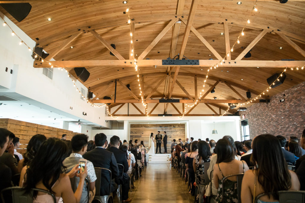 Modern wedding ceremony lit by hanging lights and natural sunlight at The Colony House.