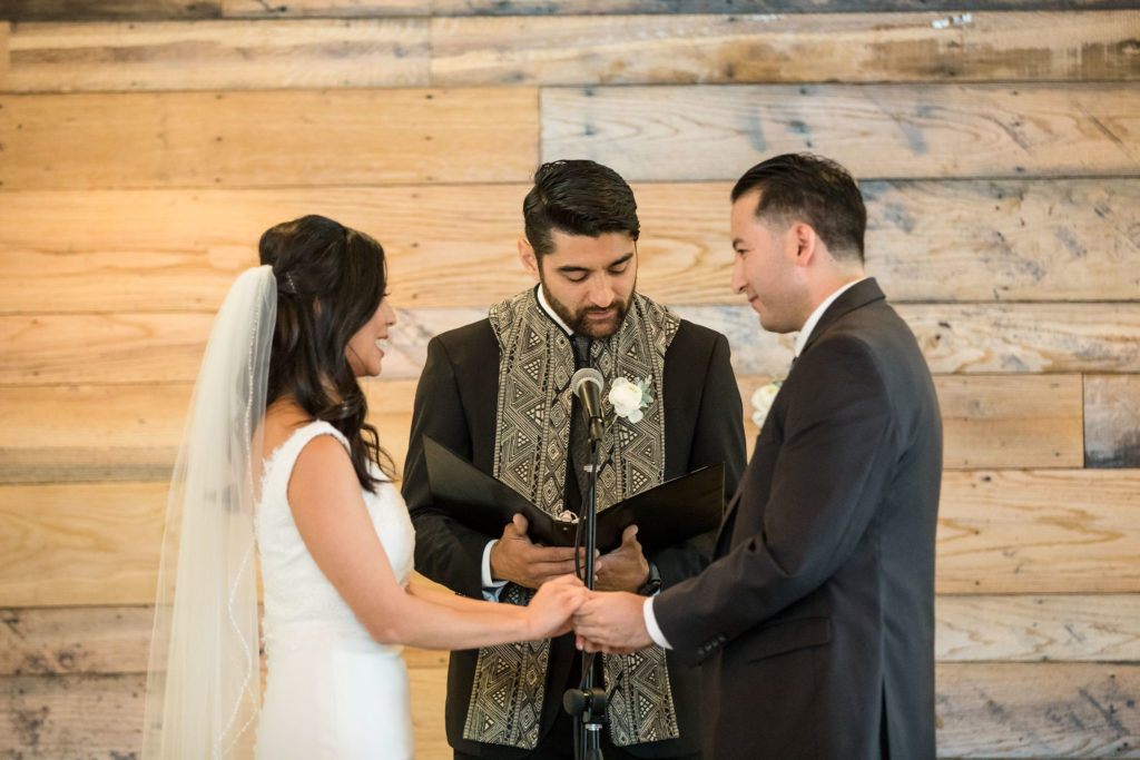 Bride and groom saying vows with rustic wooden wall background at modern wedding at The Colony House.