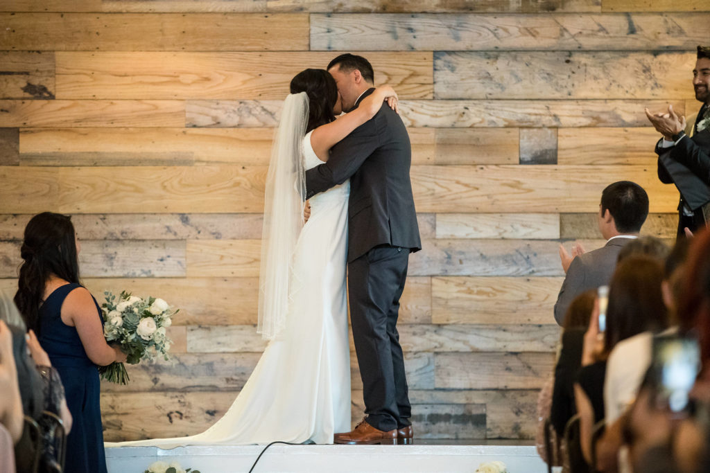 Bride and groom kiss after saying vows at modern wedding.