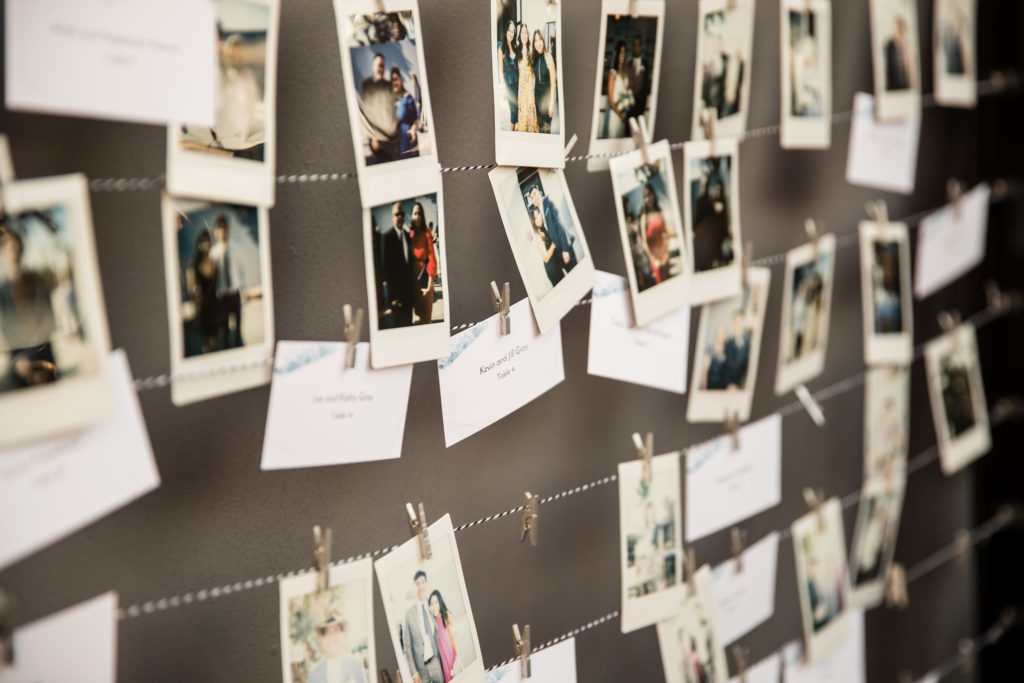Escort cards replaced with polaroid photos of guests, hung by mini clothespins and string.