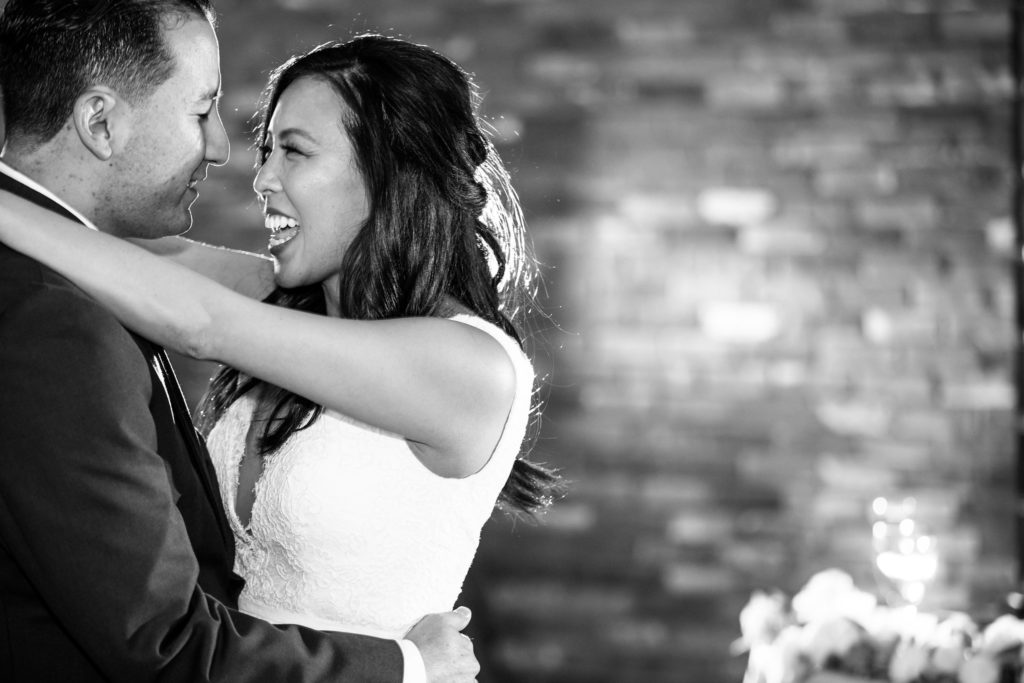 Romantic black and white photo of bride and groom singing to each other during first dance.